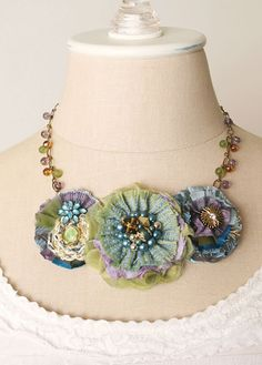 Colorful blooms featuring layers of hand cut and sewn fabrics in a rainbow of deep ocean blue hues. Pretty textures and mixed patterns, along
