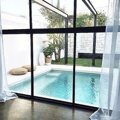 DIVINE| black sectional window bifold over looking courtyard pool with black steel framework. Design Mon Palmer.