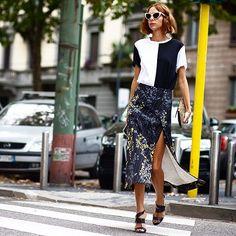 Saia mídi Marni floral com fenda, t-shirt bicolor, óculos gatinho branco, maxi clutch, sandália de salto preta. Candela Novembre inspiração MFW Streetstyle