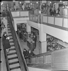 Carry on shopping - London, 1942: A wide view of the escalators at Bourne and Hollingsworth department store in London. Women can be seen travelling and up and down these wooden escalators and several of the various departments of the store can also be seen.
