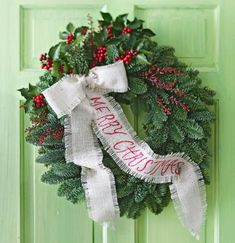 """Add a special touch to an evergreen wreath with """"Merry Christmas"""" handwritten on a burlap bow."""