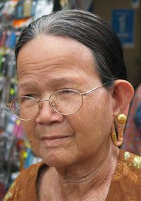 Iban woman with stretched ear piercings: Kuching, Sarawak, Malaysia, Borneo