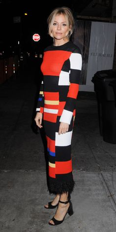Sienna Miller got graphic for the Live by Night screening in a rainbow-bright black, orange, and electric blue striped Proenza Schouler knit dress with a feather-embroidered hemline.