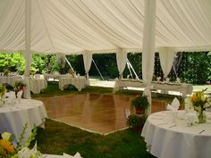 Round tables and the head table are positioned around a 16' x 18' dance floor for a wedding reception