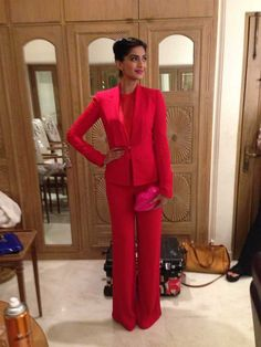 Sonam is daring and flamboyant in her fashion sense. Seen here in Ellie Saab menswear inspire blazer and wide leggy pants in scarlet red. Underneath her blazer was a matching collar lace blouse. She accessorised with a girly bright pink Lulu Guinness lip clutch.