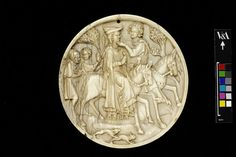Carved ivory mirror case.  Depicts a hunting scene where the woman is wearing a bycocket.  Paris, France 1330-1350 (made)