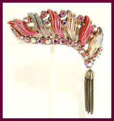 SCHIAPARELLIBROOCH AND EARRINGS, Hot Rose Pink iridescent  curved and twisted stones and iridescent Cream colored twisted stones with aurora borealis Hot Pink rhinestones with a gold tone tassel.     Marked on the back Schiaparelli in Script.