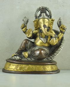 Auspicious Ganesh Antique Brass Statue. • We love Ganesh - the chubby, gentle, wise, elephant-headed deity, known as the remover of obstacles. • Ganesh, or Ganesha, son of Lords Shiva and Parvati, is the deity whom worshippers first acknowledge when visiting a temple. • We love this reclining statue of Ganesh in blessings and abundance mode. • Each piece is individually cast of heavy recycled brass and detailed with a fine antique patina finish. • Ganesh is associated with Om, is the…