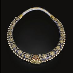 An enamelled and gem-set torque (hasli), India, Jaipur, 19th century.      of rigid ovoid from, with an applied diamond-set rosette to the centre and bridge and pin clasp, the upper side decorated with diamond flowerheads and leaves reserved against a blue enamelled ground, the reverse decorated in red, green, white and blue enamels with cartouches of alternating flowerheads flanked by birds, the edges bordered with pale blue enamelling and pearls