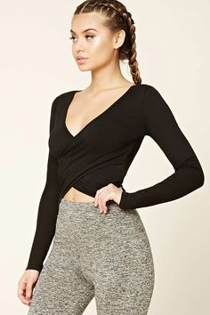 A ribbed knit athletic top featuring a surplice front, cropped silhouette, a deep V-neckline, and long sleeves.
