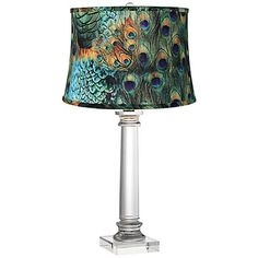 A grooved crystal rod provides the glimmering column-style base on this modern table lamp paired with a chic peacock print drum lamp shade by Vienna Full Spectrum.