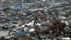 A man stands atop debris as residents salvage belongings from the ruins of their houses after Typhoon Haiyan battered Tacloban city in central Philippines November 10, 2013. REUTERS/Erik De Castro, courtesy Trust.org.