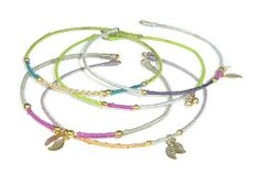 Set of 3 gold plated bangle bracelets wrapped with silk in several colors and decorated with gold plated charms. Every piece is unique and handmade. For more designs see www.SophisticatedGold.nl