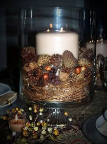 In the bottom of the hurricane holder is grapevine topped with pinecones and acorns completed with a three wick cream candle.