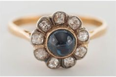A cabochon-cut sapphire, rose-cut diamond, and gold ring.