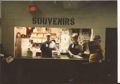Tom Torpy at his souvenirs stand by 1B. With Mike Mahler & Dennis Uczen. 1990. From the Michael Ginsburg treasury.