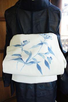 わずかに青みを帯びた白色の地に、心に染み入るような澄んだ青も美しく、露草のような可憐な草花模様が染め出された絽の夏の名古屋帯です。
