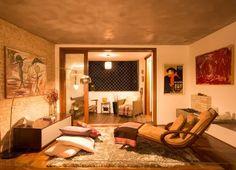 Sala de estar aconchegante. Parede de tijolinhos originais descascados, piso de madeira, cimento queimado no teto. Porta de vidro com moldura em madeira.