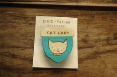 Recognize a Cat Lady in your life by giving them this sweet badge of honor - or get it for yourself, you crazy cat lady! Lovingly hand-painted, with 3 coats of varnish to protect it from the elements! The background is a nice teal color, which will stand out nicely on all your favorite cardigans....