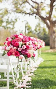 Bright pink wedding ceremony flowers adorn white chairs for a pretty contrast again the greenery