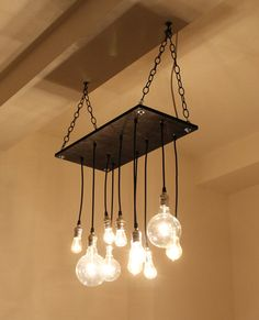Handmade  chandelier has industrial feel. Made from rescued/reclaimed plywood and recycled lamp parts.