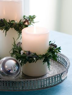 Evergreen clippings and wire come together and form tiny wreaths to slip over pillar candles. Place on a metal or silver tray to dress up the coffee table.