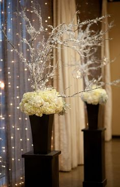 black and white winter altar floral with snowy branches and hanging candle orbs