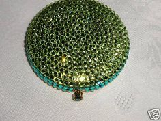 Brand New! From the ESTEE LAUDER collection comes this beautiful and highly collectible compact/powder case. It is new--was never used . This is done in a lovely golden tone with many sparkling green