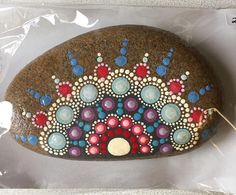 An original hand painted mandala stone in vibrant colors. Each stone is sealed with an acrylic spray and comes with a card explaining the history of the good fortune mandala stone.