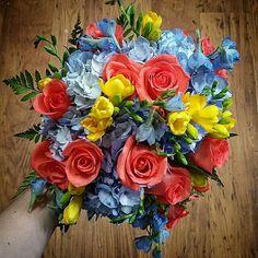 Blue Hydrangea, Blue Delphinium, Yellow Freesia, Deep Coral Roses + Green Leather Leaf Fern Wedding Bouquet