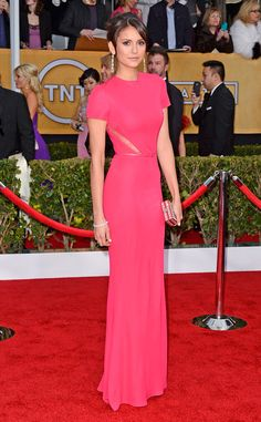 Nina is wearing a bright pink Elie Saab short sleeve gown with sheer lace tiny slit cutouts on the side. She looks elegant and beautiful! Of course I love the color pink.