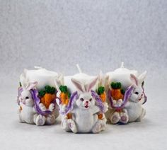 Three super cute bunnies linked by a lavender ribbon carry a heavy burden of carrots.