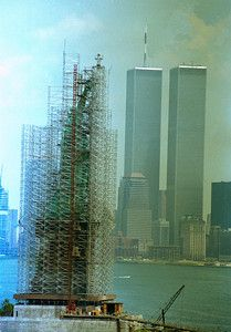 The Statue of Liberty is completely covered in scaffolding during restoration work on the 99-year-old statue in New York in 1985. The Lower Manhattan skyline, with the twin towers at the World Trade Center can be seen in background. (AP Photo/Richard Drew)