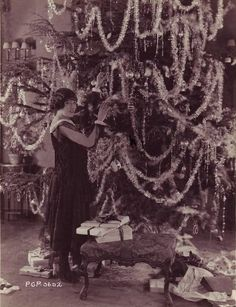 Gloria Swanson decorates her enormous Christmas tree!    I wonder if this shot is from the Christmas she spent in France? She described having an absolutely enormous tree that year.