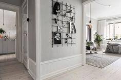 jasne szare ściany, wysokie białe listwy przypodłogowe,druciana kratownica na wieszanie zdjęć i dekoracji na ścianie w przedpokoju - Lovingit.pl