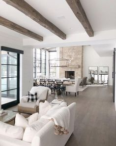 modern farmhouse living room decor with white sofa, stone fireplace, ceiling beams, neutral living room decor
