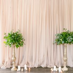 taupe curtain backdrop with candlesticks and greenery
