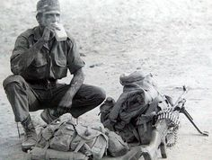MANY GOOD PICS OF MAG GUNNERS, BUT THIS IS THE BEST ONE.   THE EYES.....THE SWEATBAND....THE BUSH HAT WITH DAY-GLOW PATCH WORN OUT....THE GRIT AND DUST ON THE SKIN, THE WORN AND WEARY BOOTS ....THAT SMALL PLASTIC BOTTLE (HIS MOM HAS SEND HIM OFF TO SCHOOL WITH IT, COLD MILK OR OROS). THE TORN AND TATTERED BROWNS.