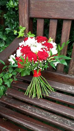 A gorgeous hand tied bouquet of Red Naomi roses and ivory freesia wrapped in scarlet voile ribbon.