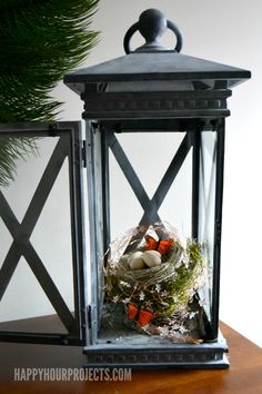 A cute little nest, a butterfly, some moss garland and star string lights inside a traditional lantern for spring mantel decor.