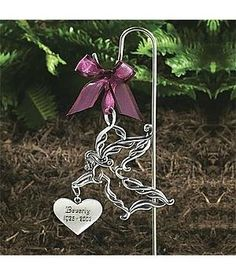 Personalized Memorial Garden Stake by Personal Creations. $19.99. Place This Lovely Pewter Stake In Your Garden Or At The Grave Site As A Constant Reminder Of Your Departed Loved One. Scrollwork Angel Hangs From A Burgundy Organza Ribbon And Holds A Dangling Heart Engraved With Your Message. Makes A Thoughtful Gift For A Friend Or Family Member In Mourning.