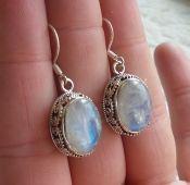 Zilveren oorbellen met regenboog Maansteen in bewerkte setting