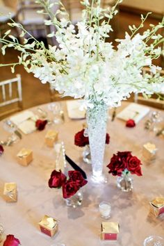 make the tall vase full of black and white feathers with a few red rose buds and clear votives! great for my hollywood wedding centerpiece!