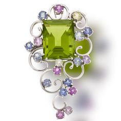 A peridot and multi-colored sapphire brooch