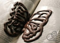 Chocolate butterflies - Wax paper on an open book and a piping bag of chocolate.