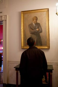 On a tour of the State Floor of the White House, President Barack Obama looks at a portrait of John F. Kennedy by Aaron Shikler and hung up in the Cross Hall, 01/24/09.