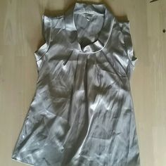 Silver, metallic color top, size M Dress it up or dress it down- your choice. Ties in the back, 100% polyester, sleeveless, slight cowl neck look, excellent condition Speechless Tops Blouses