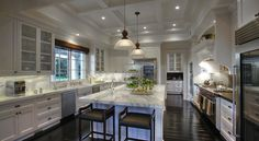 kitchens - coffered ceiling glass-front fridges farmhouse sink flanked stainless steel dishwashers floor to ceiling white kitchen cabinets kitchen island marble slab backsplash countertops glossy brown wood floors