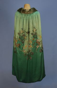 BEADED and EMBROIDERED SILK EVENING CAPE, 1920's. Two shades of green satin embroidered in pastel silk and chenille, with gold metallic threads, having bronze seed and crystal bugle beads and sequins in an undulating pattern of swallows, flowers and butterflies, with panne velvet lining and ruched collar.