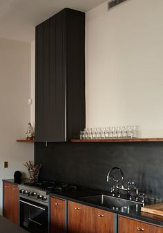 Glasses stacked on shelf above bench & matte black splashback along full wall